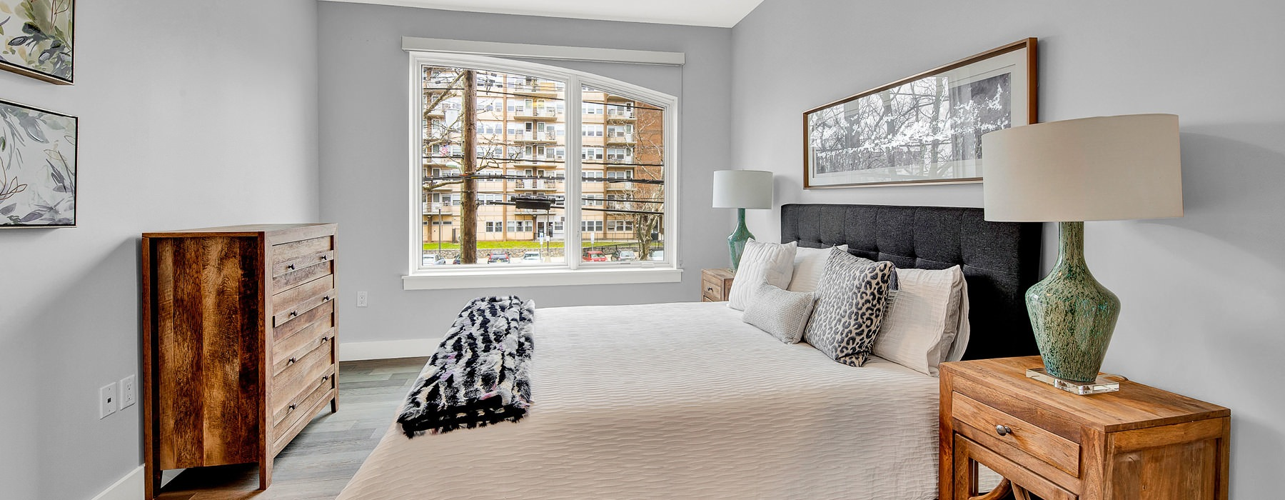 spacious master bedroom with light fixture and large windows